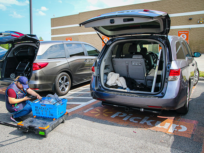 Person loading shopping into the back of an open car