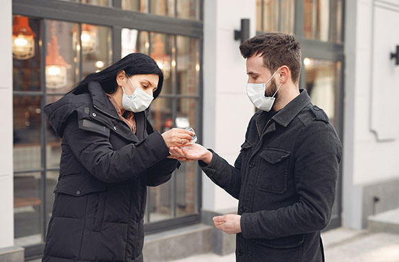Two people wearing face masks using hand sanitiser