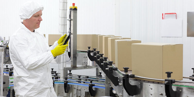 Man working on production line holding a tablet, in a white lab uniform and yellow gloves. Cardboard boxes are on the production line.