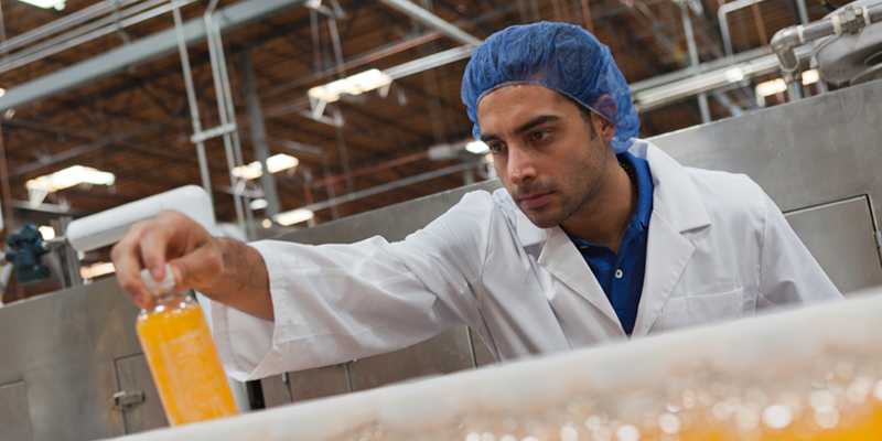Man in white lab coat and blue hair net picking and looking at orange drink on production line
