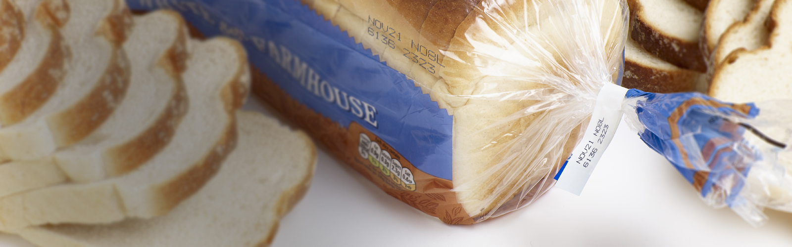 Blue cij printer code on clear bread packaging, including best before date
