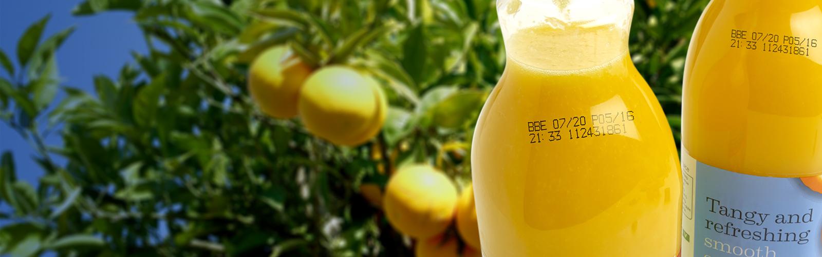 Black continuous inkjet printer code on plastic orange juice bottles, including best before date