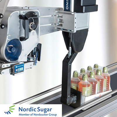 Domino M230i-S4 applying label onto Nordic Sugar packaging tray