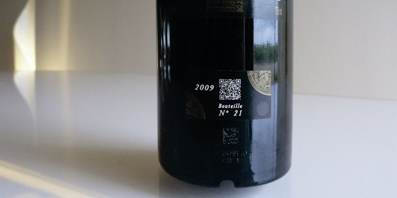 Glass bottle of red wine with white QR code printed on the side